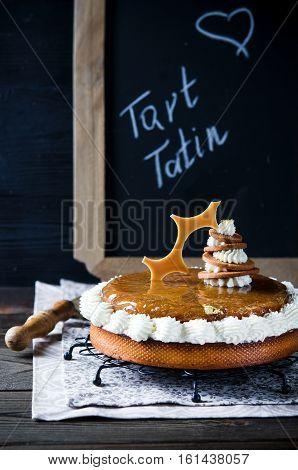 Tarte Tatin with Chantilly cream and almond frangipani on dark wooden background