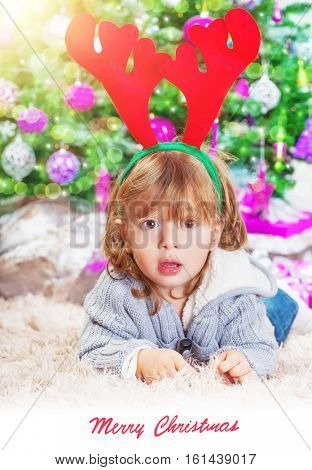 Little boy lying down near Christmas tree at home, little Santa helper, reindeer head accessory, Christmastime photo with text space, celebrating winter holidays