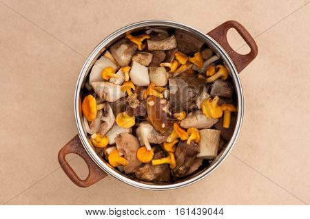 Raw Fresh Edible Mushrooms Chanterelles And Clean Cut Porcini In Large Metal Kitchen Pot Pan On Beige Brown Background Top View.