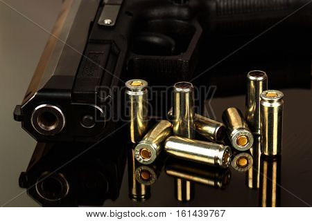 The black gun and cartridges on a black background close up.