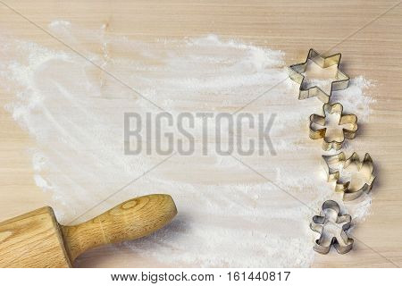 Cookie cutter mold and wooden rolling pin on a floured wooden board. Free place for your text is in centre of the photo.