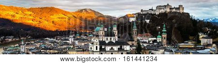 Salzburg landmarks in Austria. Aerial view of Salzburg Austria at sunset. Castle and Cathedral with mountain at the background