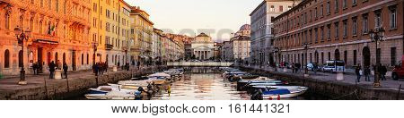 Trieste Italy. Church of St. Antonio with Channel Grand in the evening in Trieste - port town in Italy. Sunset sky with boats and illuminated buildings
