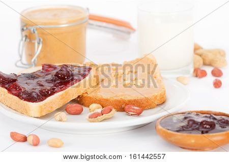 Creamy peanut butter in a jar, peanut butter & jam sandwich and glass of milk on white