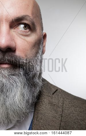 Closeup of a bald man with long beard, half face