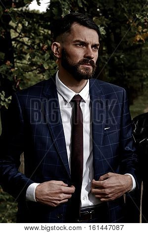 brutal man in suit with beard and mustache