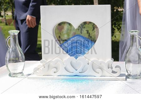 Marriage ceremony. Glass box with colourful sand on table