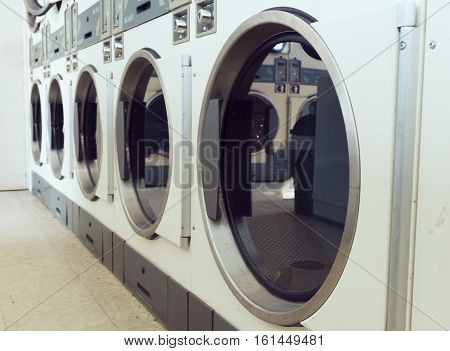 industrial line of laundry machines in laundromat store