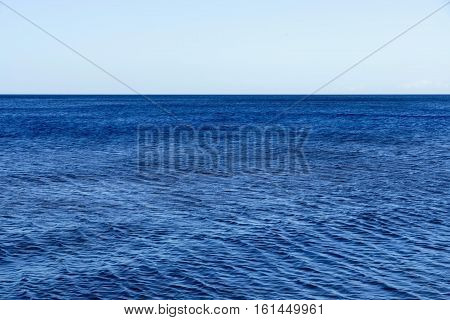 big blue surface of the water with ripples and the line of the horizon with a clear sky for a natural background