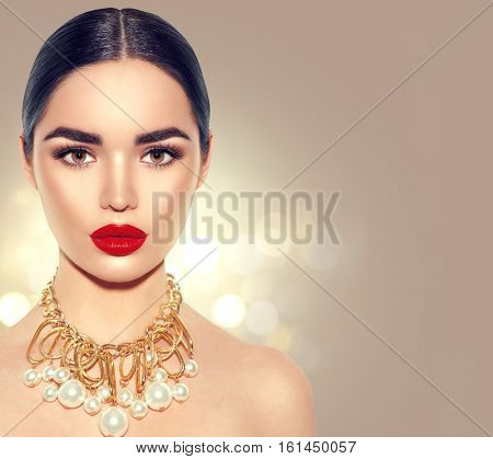 Gorgeous Young Brunette Woman face portrait. Beauty Model Girl with perfect bright make-up, red lips, golden jewellery with pearls. Sexy lady makeup for party. Holiday  golden background.