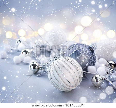Silver Color Christmas and New Year Decoration on blurred grey background with lights. Border art design, holiday bauble. Beautiful Christmas ball closeup decorated with tinsel. Space for your text.