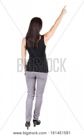 Back view of young brunette woman in trousers pointing at wall. beautiful girl. Rear view people collection. backside view of person. Isolated over white background.