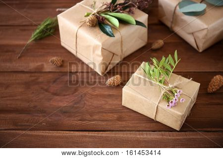 Handcrafted gift boxes with flowers on wooden table