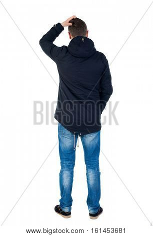 Back view of handsome man in winter jacket  looking up.   Standing young guy in parka. Rear view people collection.  Isolated over white background. Man in warm jacket scratching top of the head arm.
