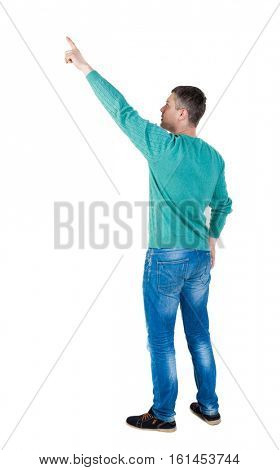 Back view of  pointing young men in jeans. Young guy  gesture. Rear view people collection.  backside view of person. The guy in the green jacket stands sideways and shows a finger at right