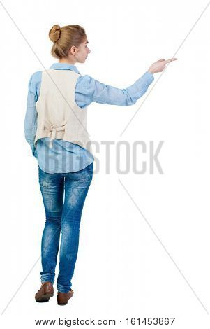 Back view of  pointing woman. beautiful girl. Rear view people collection.  backside view of person.  Isolated over white background. Girl in sleeveless shows a finger to the left.
