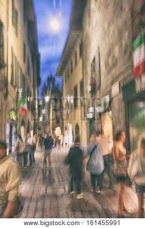 Evening life of tourists on the street with shop windows and restaurants and flags in the ancient city of Bergamo in Italy
