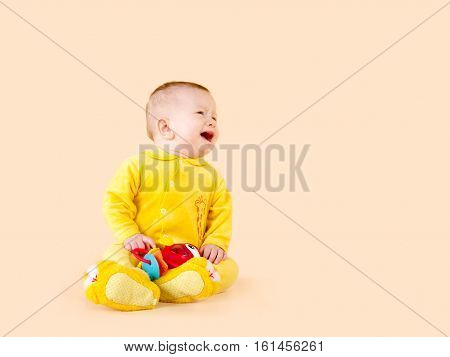 small child crying. Baby bright yellow suit red toy. Beige background