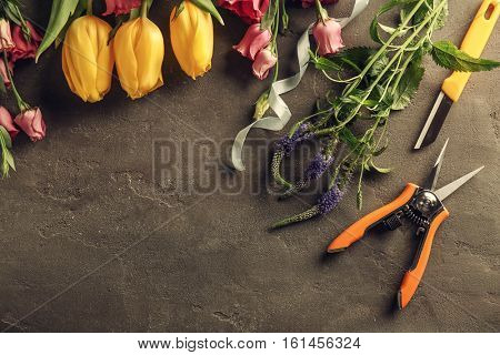 Beautiful flowers and florist equipment on dark background