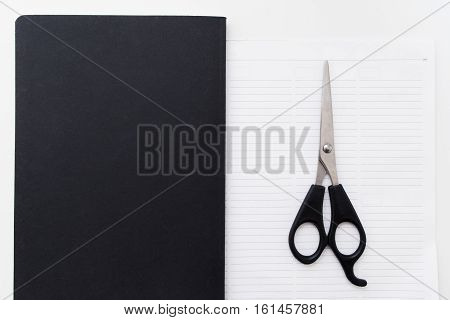 Scissors on blank notepad flat lay free space. Top view on open blank notebook with cutter on first page. Business, stationery, modern life, contrast, brend book, deliverance concept concept