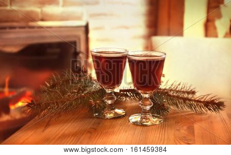 Glasses of mulled wine and coniferous branch on wooden table against blurred fireplace