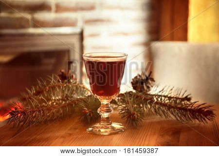 Glass of mulled wine and coniferous branch on wooden table against blurred background