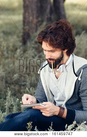 Close-up of thoughtful man with notebook biting pencil. Attractive bearded guy writing, drawing, counting in his sketchbook at nature, copy space.