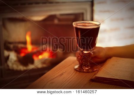 Female hand and glass of mulled wine with blurred fireplace on background
