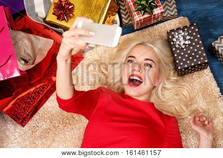 Beautiful young woman taking selfie while lying on floor among shopping bags and Christmas presents