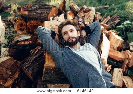 Portrait of attractive man lying on pile of wood. Fashion picture of very masculine guy having rest after hard work on firewood bunch. Manhood, strength, handiwork concept
