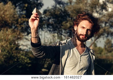 Young pleased guy playing outdoor with paper airplane. Portrait of bearded man with handmade paper plane in hands, aiming to sky, squinting in sun.