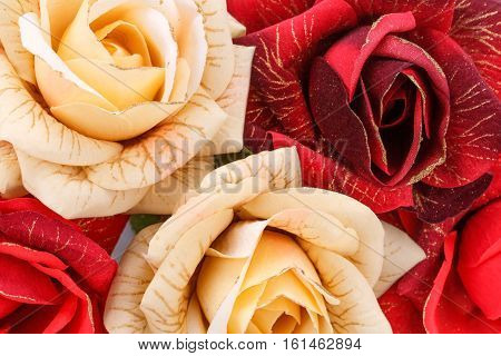 Red and yellow fabric roses closeup picture.