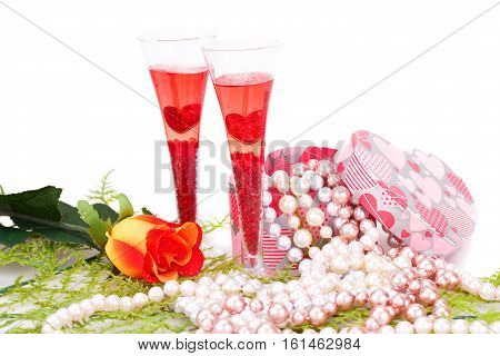 Two glasses rose colorful pearls necklaces and gift box on white background.