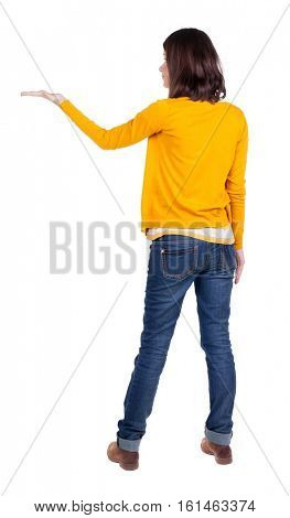Back view of Beautiful business woman in yellow pulover looking at wall and Holds a hand up.  young brunette girl standing. Rear view people. Isolated over white background.