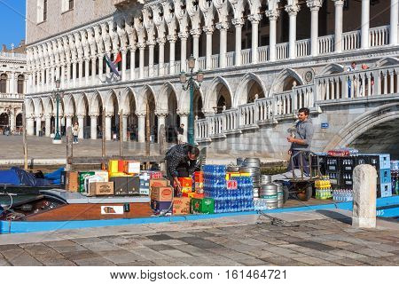 Venice Italy - May 05 2016: Workers unloading goods from delivery boats near St. Marks Square of Venice