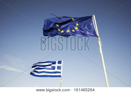 Ripped european Union flag and Greek flag waving in the wind