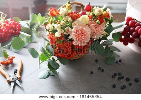 Beautiful flower composition with berries on table
