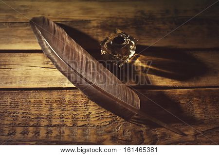 Feather pen and inkwell on wooden background
