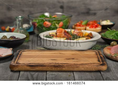 Cutting board on wooden kitchen table in the background baked chicken legs in a baking dish with variety food