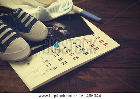 Calendar with ultrasound scan of baby and children shoes, closeup