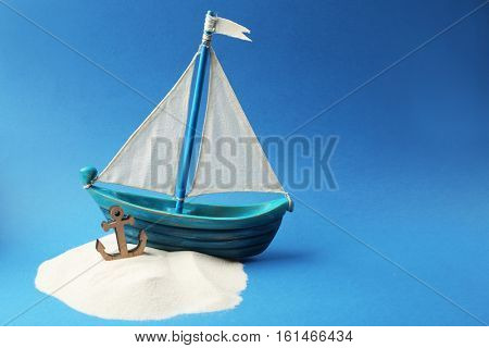 Wooden boat, anchor and sand on blue background. Columbus Day concept