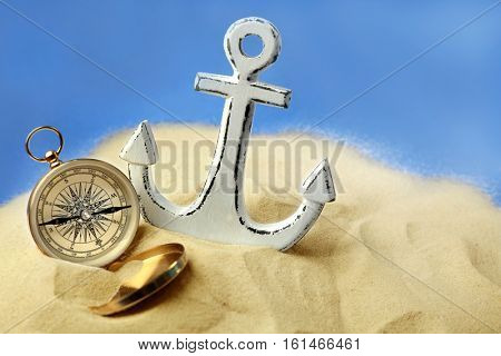 Anchor and compass in sand on blue background. Columbus Day concept