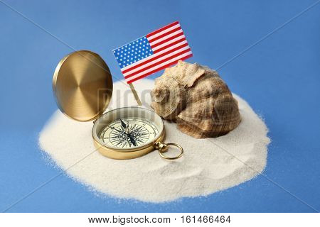 USA flag, compass and shell in sand on blue background. Columbus Day concept