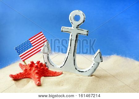 Anchor, starfish and USA flag in sand on blue background. Columbus Day concept