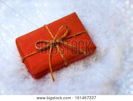 Gift wrapped in paper in the snow. Christmas gift in red paper.