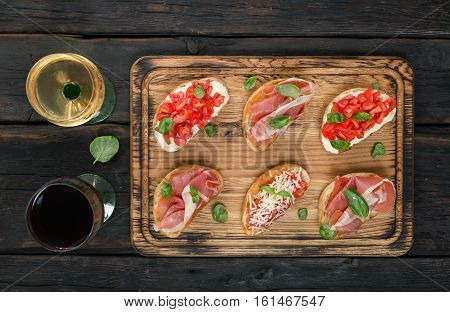 Set of small sandwiches with jamon tomatoes parmesan cheese fresh basil served with glass of red and white wine on wooden board top view