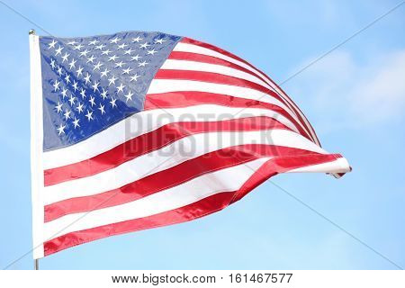 Ruffled American flag on blue sky background
