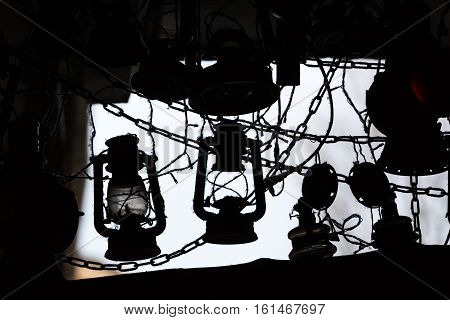 background of many lit storm lanterns or hurricane lamps