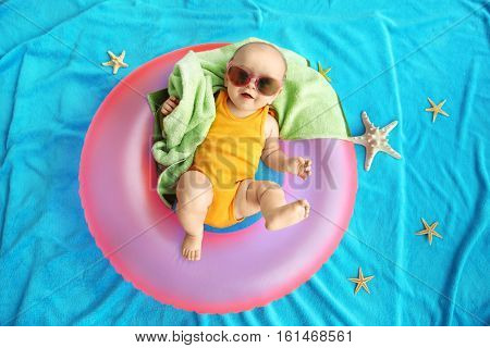 Cute baby with swimming ring, towel and sunglasses lying on blue bedspread. Holidays at sea with baby, concept