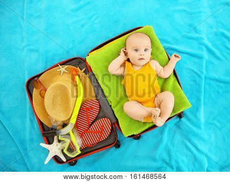 Cute baby and things for vacation in suitcase lying on blue bedspread. Holidays at sea with baby, concept